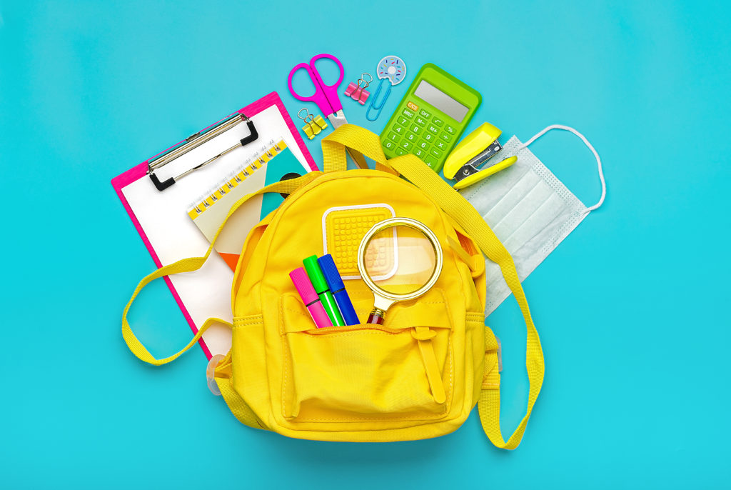 Back to school, education concept Yellow backpack with school supplies, protective medical mask, calculator, scissors isolated on blue background. Top view Copy space Flat lay.