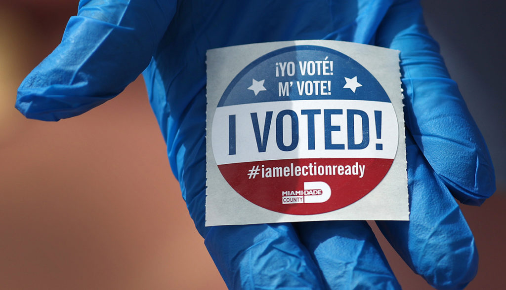 MIAMI BEACH, FL  - MARCH 17:  A voter holds an, 'I Voted!', sticker after wearing a glove as she cast her ballot during the Florida presidential primary as the coronavirus pandemic continues on March 17, 2020 in Miami Beach, Florida.  People are heading to the polls to vote for their Republican and Democratic choice in their parties' respective primaries during the COVID-19 outbreak. (Photo by Joe Raedle/Getty Images)