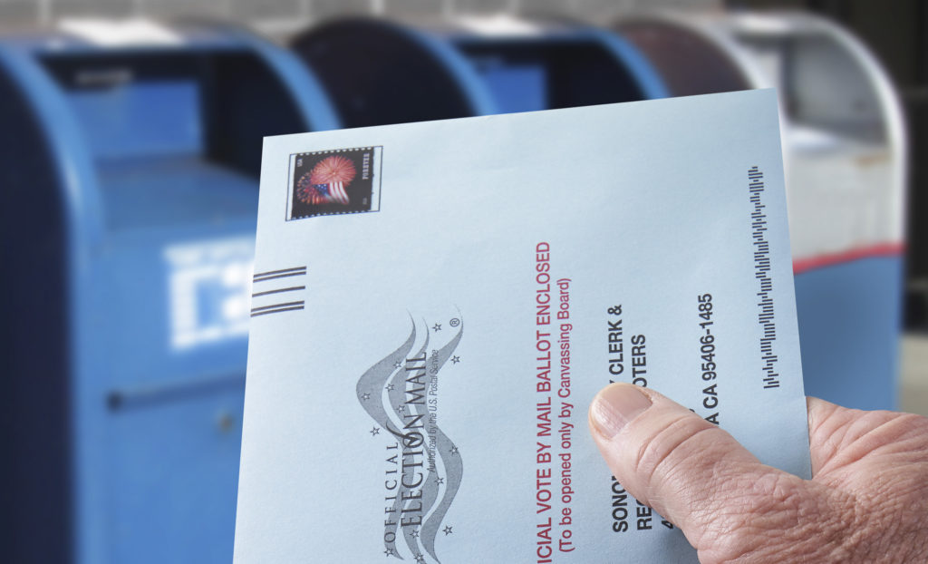 THE SEA RANCH, CALIFORNIA - October 21, 2018: Voting ballot: Absentee voting by mail with hand holding envelope by mailboxes. Absentee voting is voting-by-mail and allows voters who cannot visit the polls on Election Day, to cast their ballot by the US mail.