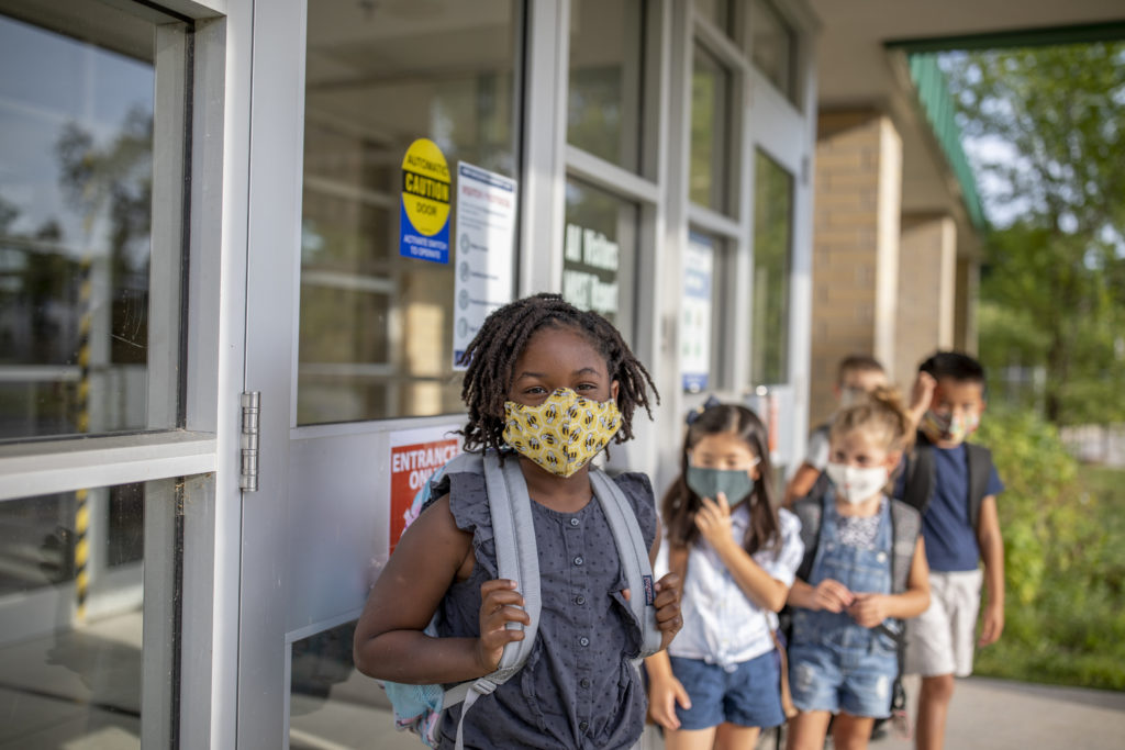 Group of kids return to school during the pandemic.